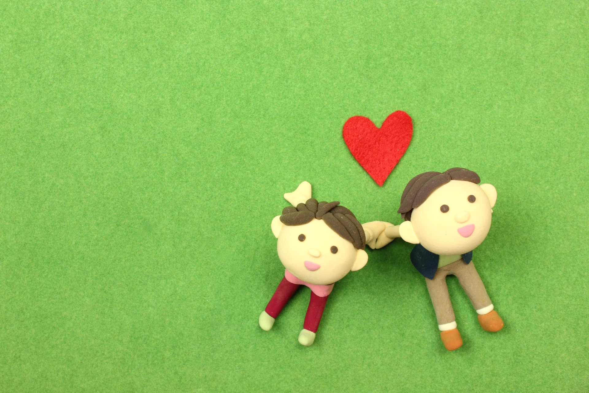 芝生に座るカップルのフェルト人形